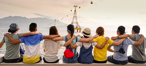 A group of friends, arms locked, sitting on a wall, looking at the Eiffel Tower