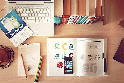 Books, compuyers, cell phone, desk accessories on a desk