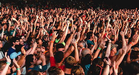 A crowd of people with hands in the air